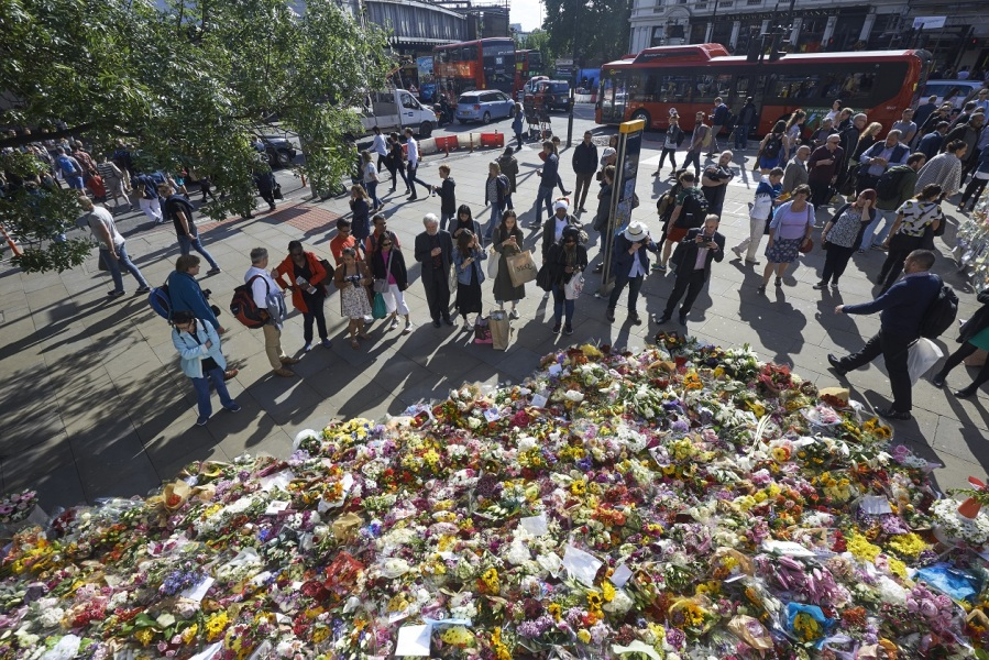 Pedestrians stop to look at floral tributes left by well-wishers on London bridge in London on June 9, 2017, following the June 3 terror attack that targeted members of the public on London Bridge and Borough Market.  Niklas HALLE'N / AFP