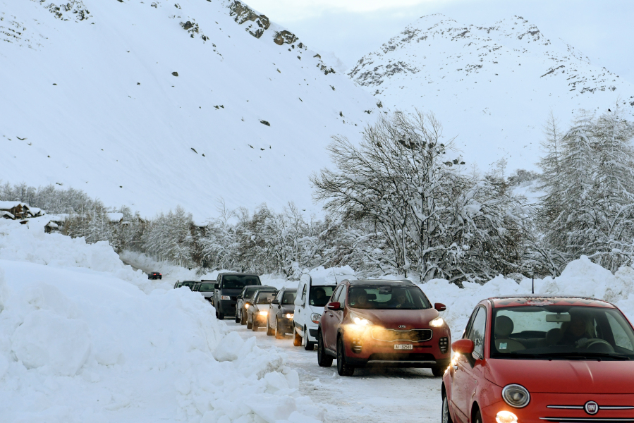 Cars drive in a convoy from Bessans to Bonneval-sur-Arc in the French Alps on January 12, 2018 through a road that has been temporarily re-opened, after being cut off following an avalanche.