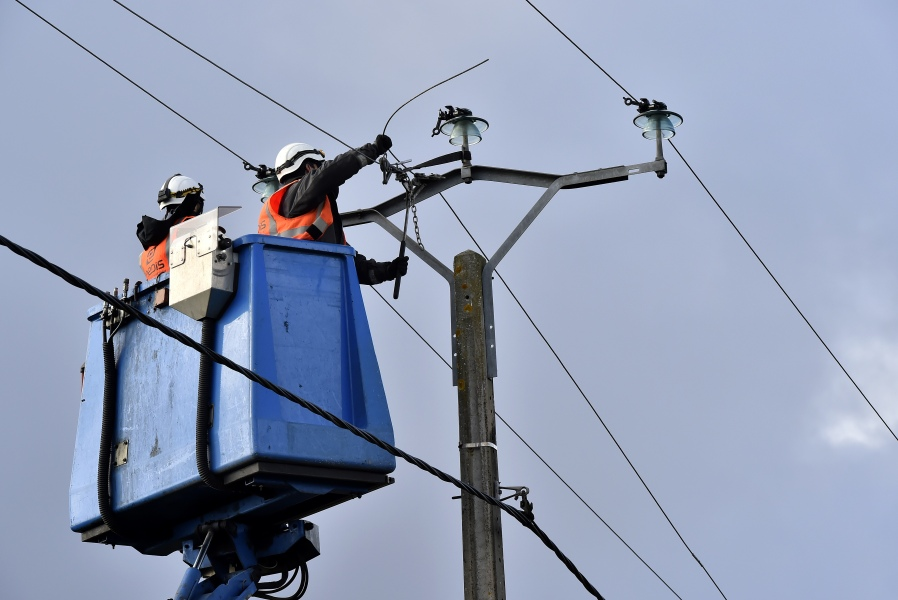 French national electricity grid Enedis' technicians work on an electric line on February 5, 2017 near Begadan, southwestern France as high winds damaged infrastructures.