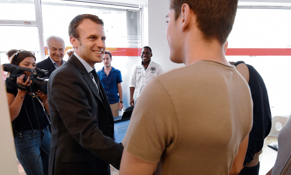 French Economy Minister Emmanuel Macron (L) speaks with young people during a visit to Be Web in Lunel on May 27, 2016.  SYLVAIN THOMAS / AFP