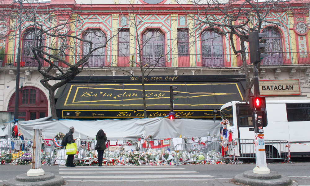 A general view taken on December 13, 2015 shows people paying tribute to victims in front of the music hall Bataclan a month after the Paris terror attacks on November 13, 2015. France voted on Sunday with the far-right National Front (FN) hoping to win control of a region for the first time, giving leader Marine Le Pen a launchpad for her presidential bid in 2017. Voting opened amid heightened security, especially in Paris, as France remains under a state of emergency declared after the November 13 attacks that claimed 130 lives. AFP PHOTO / MATTHIEU ALEXANDRE 