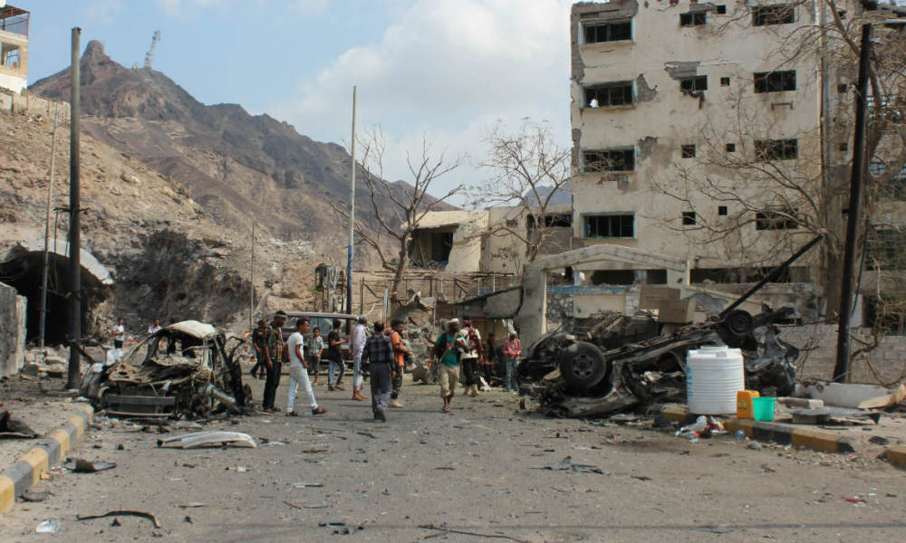 Armed Yemeni men look at the wreckage of a vehicle on January 18, 2016, in the aftermath of a suicide car bombing on the residence of Aden's police chief, General Shalal Shaea. Eight civilians and two guards were killed, while the police chief was not hurt, security officials said. It was the latest attack in a wave of unrest that has rocked Aden, declared Yemen's provisional capital after the government was forced to flee Sanaa in September 2014 after Shiite