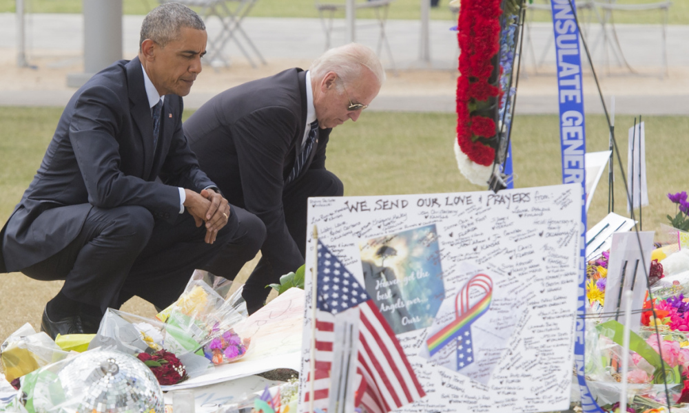 US President Barack Obama and Vice President Joe Biden place flowers for the victims of the mass shooting at a gay nightclub Sunday at a memorial at the Dr. Phillips Center for the Performing Arts in Orlando, Florida, June 16, 2016. 