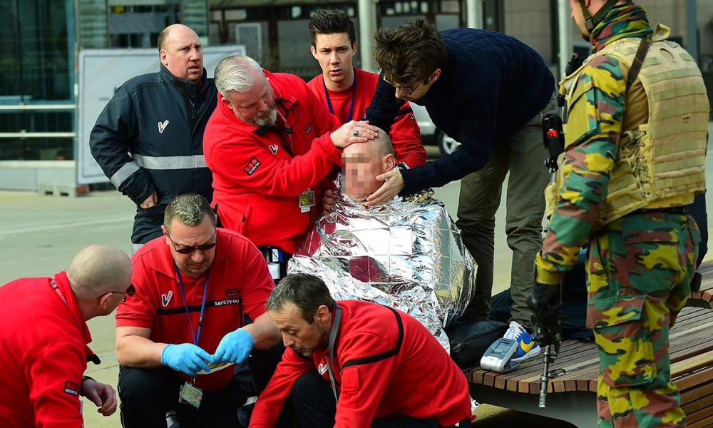 A victim receives first aid by rescuers, on March 22, 2016 near Maalbeek metro station in Brussels, after a blast at this station near the EU institutions caused deaths and injuries. AFP PHOTO / EMMANUEL DUNAND  EMMANUEL DUNAND / AFP