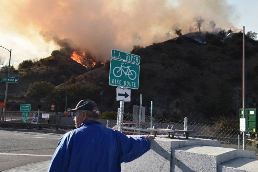 A man watches flames from a wildfire in Griffith Park in Los Angeles, California, November 9, 2018. Staff at the Los Angeles Zoo, which is located in the park are preparing animals to be evacuated. Robyn Beck / AFP
