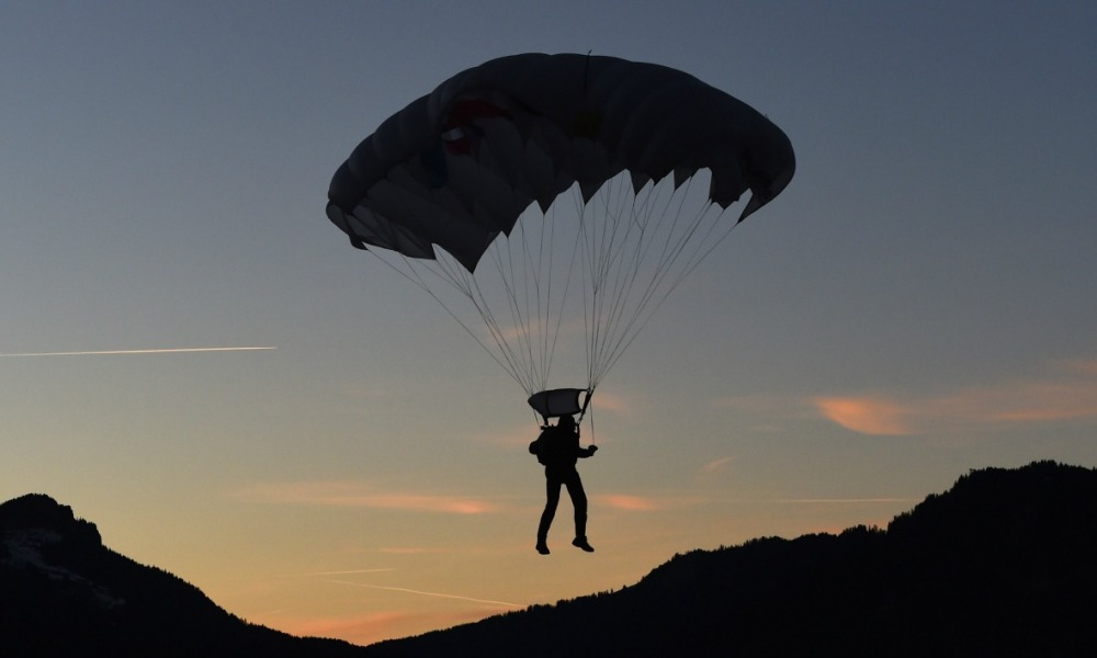 Sun sets as a paraglider prepares to land at the ski stadium prior to the ski jumping event in Oberstdorf, southern Germany, which is the first station of the Four-Hills Ski Jumping tournament (Vierschanzentournee), on December 28, 2015. The first competition of the Four-Hills Ski jumping event takes place in Oberstdorf, before the tournament continues in Garmisch-Partenkirchen, (Germany), in Innsbruck (Austria) and in Bischofshofen (Austria).