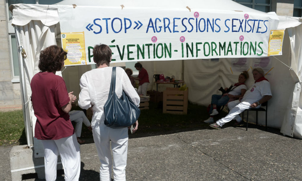 Two women stand in front of an information stand raising awareness against sexual assault and street harassment during the 81st Bayonne Festival (Fetes de Bayonne) in Bayonne, southwestern France, on July 27, 2017.  IROZ GAIZKA / AFP