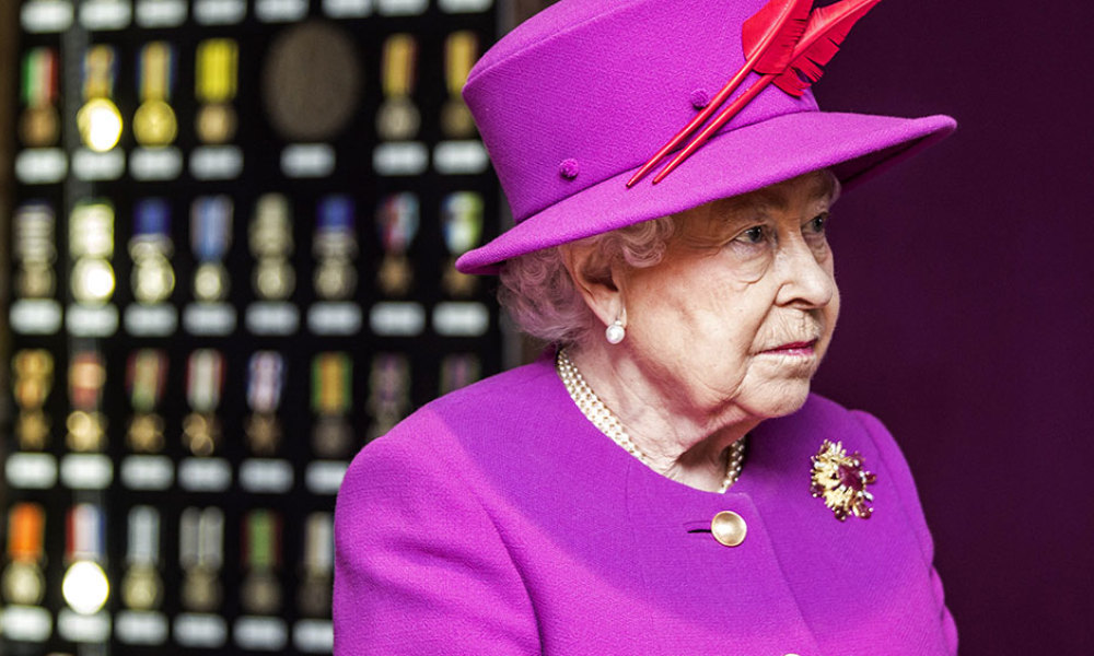 Britain's Queen Elizabeth II looks at a cabinet of medals issued during Queen Victoria's reign at the MOD Medal Office in the MOD's Defence Business Services facility at Imjin Barracks in Gloucestershire, south west England, on November 5, 2015.