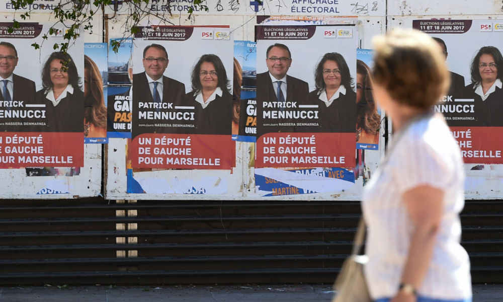 A woman walks past election posters of French Socialist MP Patrick Mennucci and fellow candidate Nassera Benmarnia in Marseille, southern France, on May 28, 2017, ahead of the upcoming French legislative elections.  BORIS HORVAT / AFP
