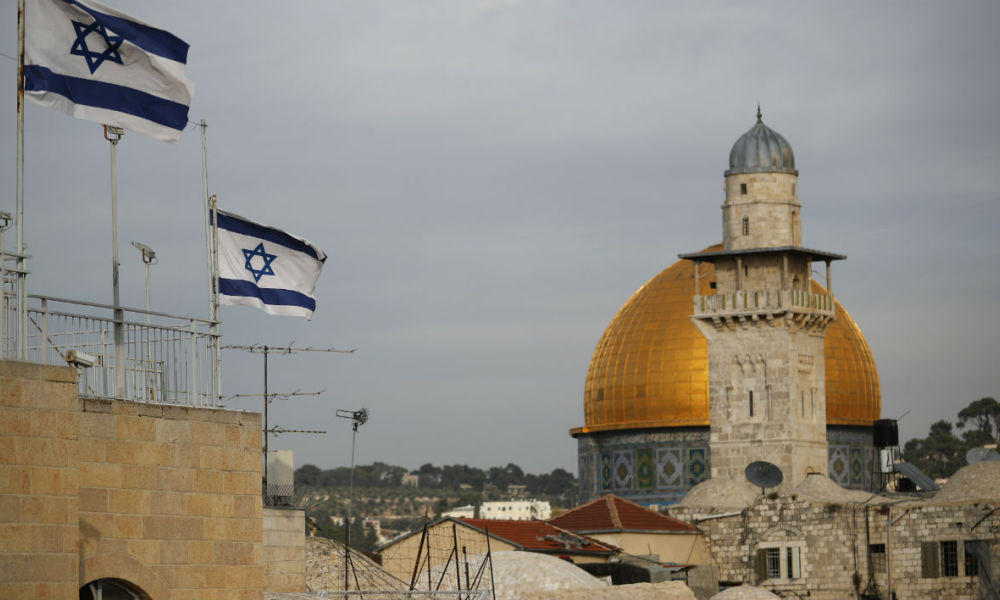 "Israeli flags fly near the Dome of the Rock in the Al-Aqsa mosque compound on December 5, 2017. The EU's diplomatic chief Federica Mogherini said that the status of Jerusalem must be resolved ""through negotiations"", as US President Donald Trump mulls recognising the city as the capital of Israel. THOMAS COEX / AFP"