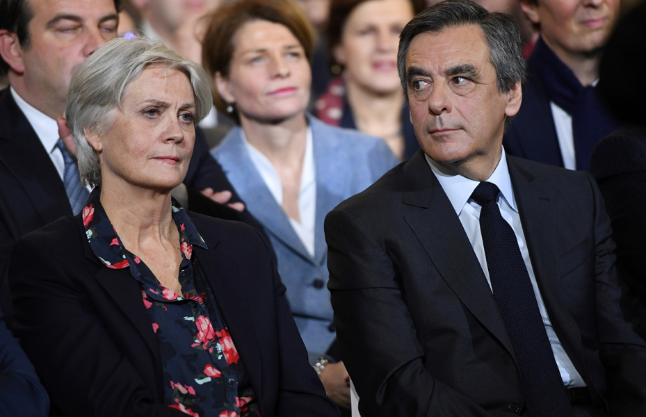 This file photo taken on January 29, 2017 shows French right wing candidate for the upcoming presidential election Francois Fillon (R) flanked by his wife Penelope (L), looking on during a campaign rally in Paris. Fillon's campaign has been struggling since it emerged that his Welsh-born wife Penelope was paid 830,000 euros (900,000 USD) as a