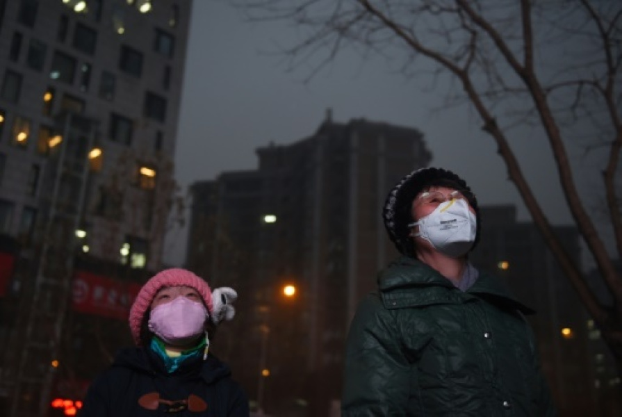Une jeune fille et une femme dans les rues de Pékin le 9 décembre 2015 Pollution red alerts spread to more Chinese cities, state media reported on December 9, as Beijing entered its third day of heavy smog, with officials warning poor co...