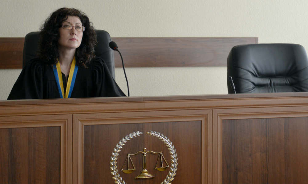 A judge of a Kiev's district court (L) asks questions to one of the two captured Russian soldiers participating in a trial by videoconference from a hospital in Kiev on May 22, 2015. A Kiev court on Friday ordered two suspected Russian soldiers who were captured by Ukrainian troops in the separatist east to be placed in pre-trial detention until July 19. AFP PHOTO/GENYA SAVILOV  GENYA SAVILOV / AFP