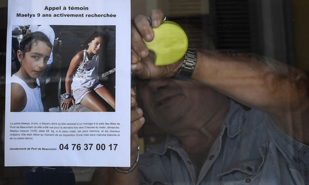 The owner of a bar attaches an appeal for witnesses poster issued by the Gendarmerie of Pont-de-Beauvoisin for Maelys, a 9-year-old girl, who disappeared during a wedding party on August 26 overnight in Pont-de-Beauvoisin, eastern France, on August 28, 2017. PHILIPPE DESMAZES / AFP