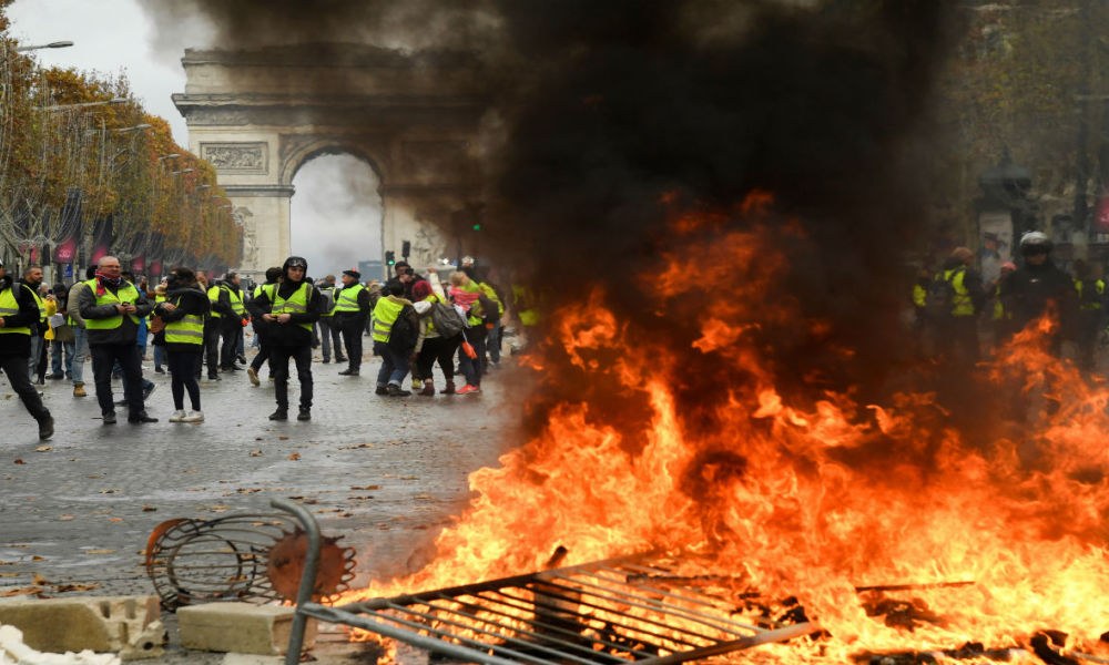Protestors stand in front of a fire of furnitures during a protest of Yellow vests (Gilets jaunes) against rising oil prices and living costs near the Arc of Triomphe on the Champs Elysees in Paris, on November 24, 2018.
