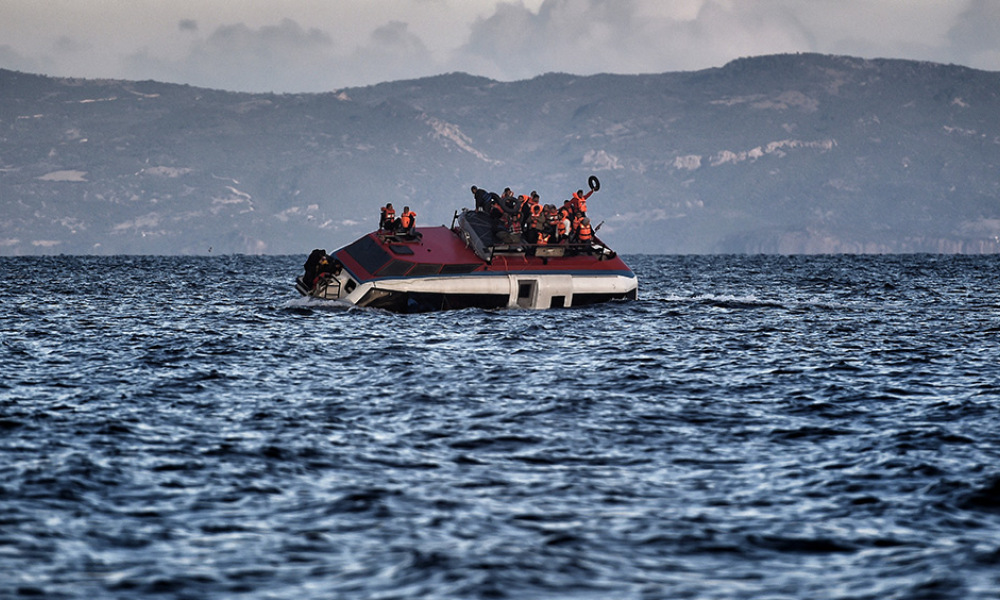 Refugees and migrants call for help as their boat is ready to sink off the Greek island of Lesbos island while crossing the Aegean sea from Turkey on October 30, 2015. More than half a million people have arrived by sea in Greece this year seeking safety and a better life in Europe, while more than 3,200 people have died making the perilous crossing from Turkey.