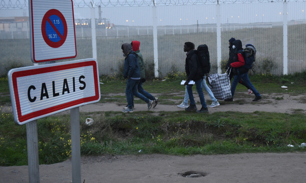 "Migrants, carrying their luggage, walk past a Calais city limit sign as they head towards an official meeting point set by French authorities as part of the full evacuation of the Calais ""Jungle"" camp, in Calais, northern France, on October 24, 2016. French authorities began on October 24, 2016 moving thousands of people out of the notorious Calais Jungle before demolishing the camp that has served as a launchpad for attempts to sneak into Britain. Migrants lugging meagre belongings boarded buses taking them away from Calais' ""Jungle"" under a French plan to raze the notorious camp and symbol of Europe's refugee crisis. FRANCOIS LO PRESTI / AFP"
