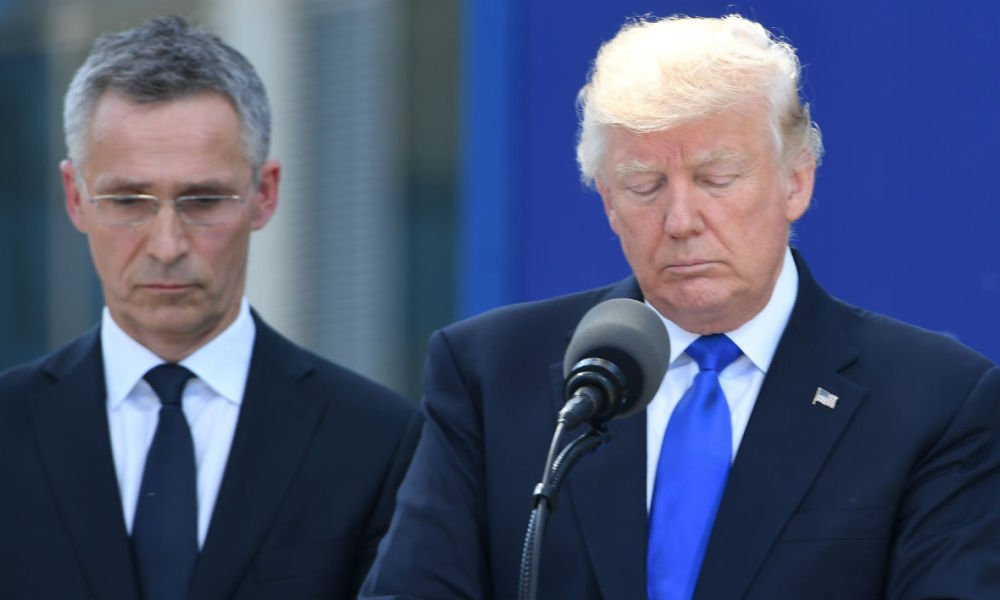 US President Donald Trump (R) stands next to NATO Secretary General Jens Stoltenberg (L) during the unveiling ceremony of the Berlin Wall monument, during the NATO (North Atlantic Treaty Organization) summit at the NATO headquarters, in Brussels, on May 25, 2017.  Emmanuel DUNAND / AFP