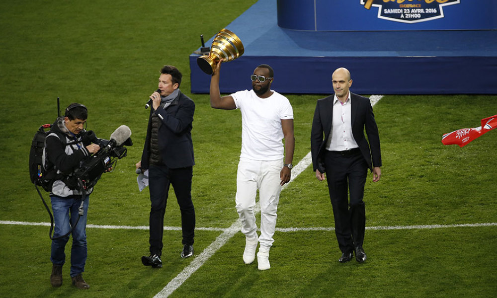 French hip-hop singer Gandhi Djuna, aka Maitre Gims (C) holds the trophy after performing prior to the French League Cup final football match between Paris Saint-Germain and Lille on April 23, 2016 at the Stade de France in Saint-Denis, north of Paris.