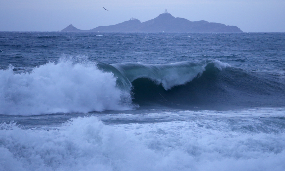 A picture shows waves crashing with the Sanguinaire islands in the background off the coast of Ajaccio, on the French Mediterranean Island of Corsica, on December 11, 2017. The island is on orange alert for waves, rain and flooding. PASCAL POCHARD-CASABIANCA / AFP