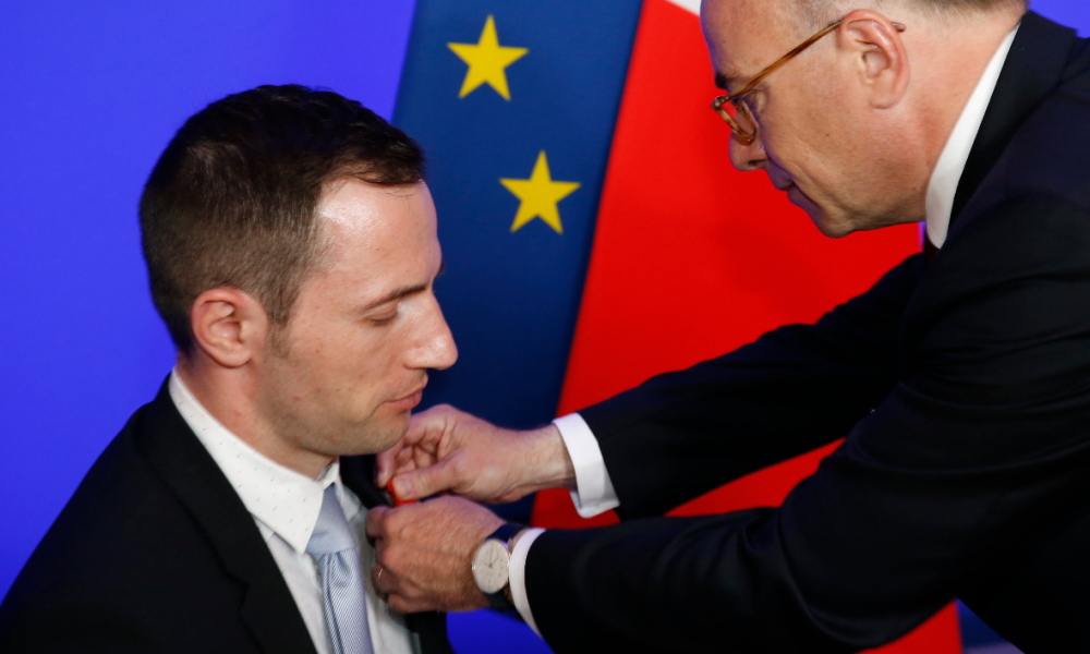 French interior minister, Bernard Cazeneuve (R) awards the Chevalier de la Legion d'Honneur (Knight of the Legion of Honour) to French Policeman Arnaud Beldon injured during November 13 Paris attacks, on June 22, 2016 in Paris.  MATTHIEU ALEXANDRE / AFP