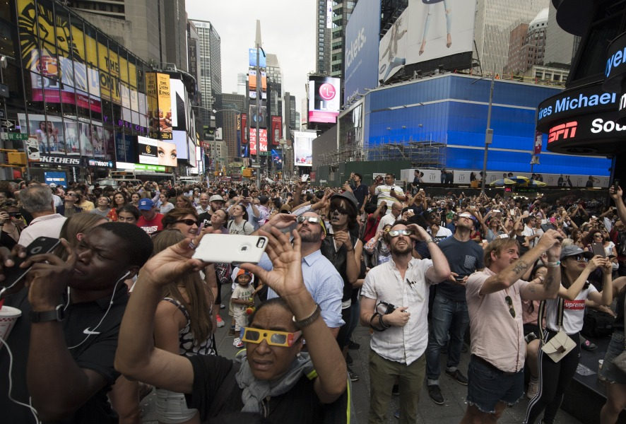 People in Times Square try to takes photos and view the solar eclipse August 21, 2017 in New York. Emotional sky-gazers stood transfixed across North America Monday as the Sun vanished behind the Moon in a rare total eclipse that swept the continent coast-to-coast for the first time in nearly a century. DON EMMERT / AFP
