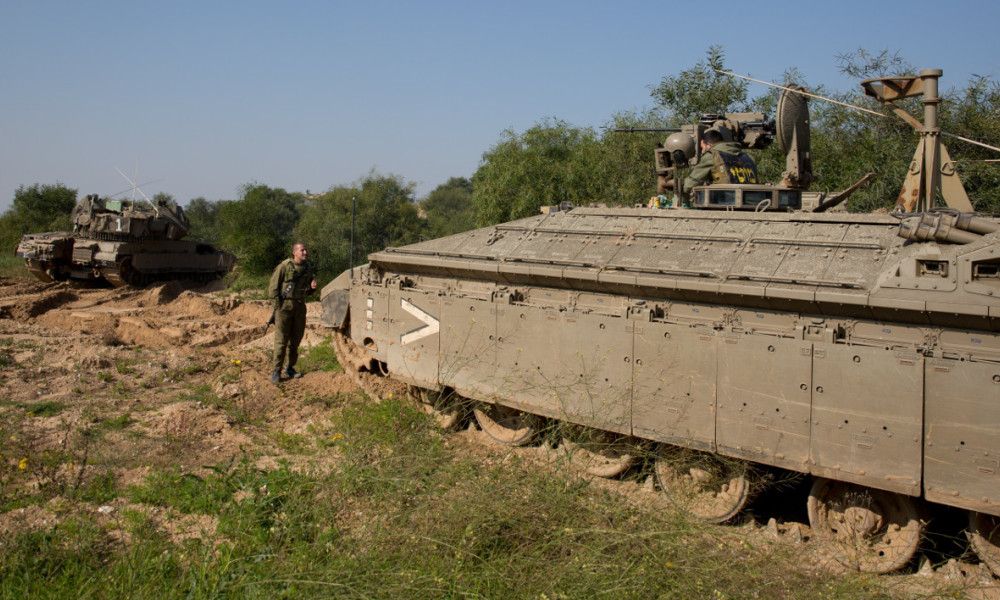 Israeli soldiers rest next to tanks on the Israeli border with the northern Gaza Strip near the southern Israeli village of Netiv Haasara on January 13, 2016. An Israeli air raid in the northern Gaza Strip targeting alleged militants killed one Palestinian and wounded three others, the Israeli army and a Palestinian official said.  MENAHEM KAHANA / AFP