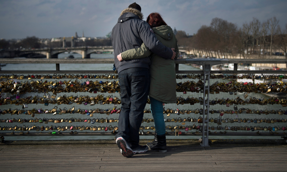 A couple enjoys the view of the river Seine from the Solferino bridge decorated with locks in central Paris on February 13, 2015. AFP PHOTO / MARTIN BUREAU  MARTIN BUREAU / AFP