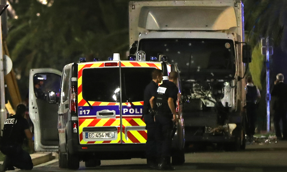 Police officers stand near a truck, with its windscreen riddled with bullets, that ploughed into a crowd leaving a fireworks display in the French Riviera town of Nice on July 14, 2016. At least 60 people were killed when a truck ploughed into a crowd watching a Bastille Day fireworks display in the southern French resort of Nice, prosecutors said early on July 15. Nice prosecutor Jean-Michel Pretre said the truck drove two kilometres (1.3 miles) through a large crowd that was watching the fireworks.  VALERY HACHE / AFP