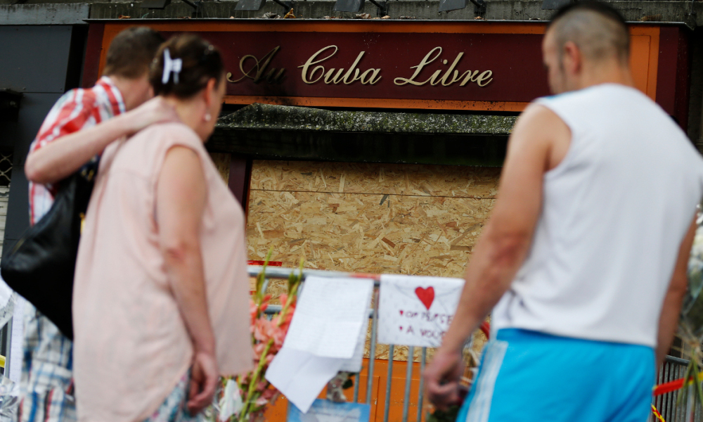 "People stand by a make shift memorial where flowers, candles and pictures are laid, in front of the ""Au Cuba Libre"" bar in Rouen, northwestern France, on August 11, 2016 after a fire sparked on August 6, 2016. A fire sparked by birthday cake candles tore through a bar in northern France on August 6, killing at least 13 people in the nation's deadliest blaze in over a decade, according to investigators. CHARLY TRIBALLEAU / AFP"