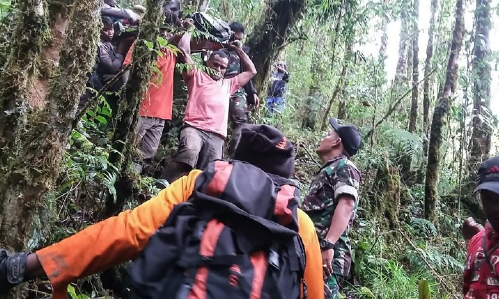 This handout photo taken on August 12, 2018 and released by the information unit of Papua's Cendrawasih Military Command shows a rescue team evacuating the sole survivor from the crash site of a Swiss-made Pilatus aircraft at Menuk mountain in Oksibil. A 12-year-old boy is the sole survivor of a plane crash that killed eight people in mountainous eastern Indonesia, authorities said on August 12. The Swiss-made Pilatus aircraft lost contact with air traffic control on August 11 during what was supposed to be a flight of around 40 minutes in remote Papua province.  Handout / Papua's Cendrawasih Military Command / AFP