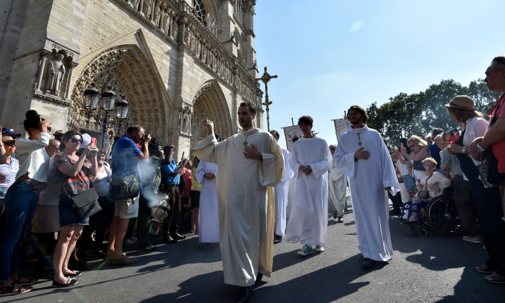 Religious men march in front of the Notre Dame Cathedral during a Catholic procession as part of the Feast of the Assumption, in Paris, on August 15, 2016.  ALAIN JOCARD / AFP