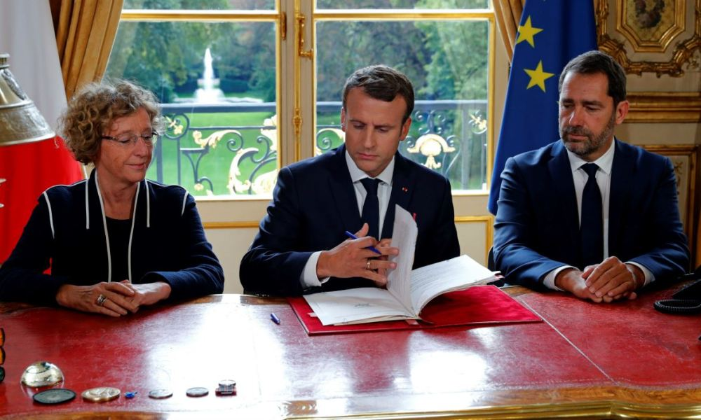 French President Emmanuel Macron (C) signs documents in front of the media to promulgate a new labour bill in his office at the Elysee Palace in Paris, on September 22, 2017, as French Labour Minister Muriel Penicaud (L) and French Junior Minister for the Relations with Parliament and Government Spokesperson Christophe Castaner (R) look on.