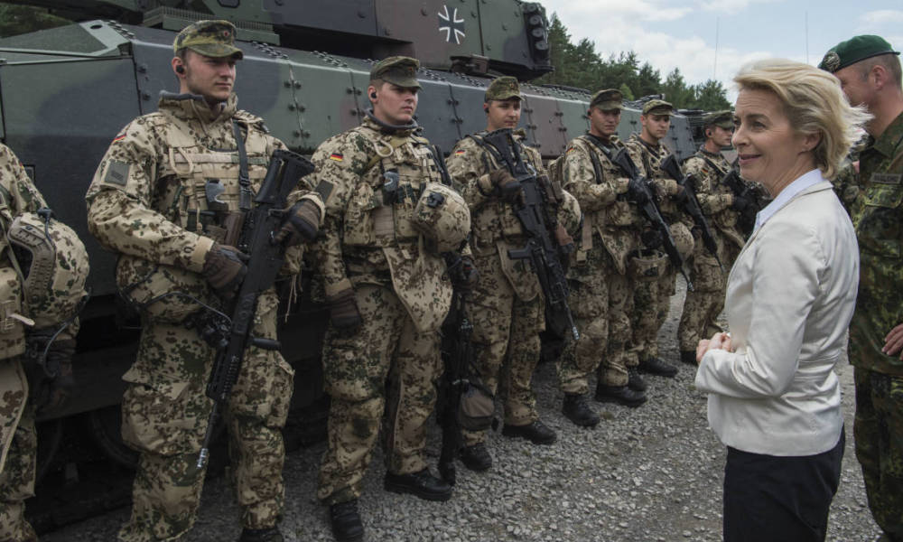 German Defence Minister Ursula von der Leyen (R) congratulates soldiers of the 33rd Panzergrenadier bataillon following a drill which involved the new Puma Armoured Infantry Fighting Vehicle (background), at their headquarters in Neustadt am Ruebenberge on June 29, 2016.