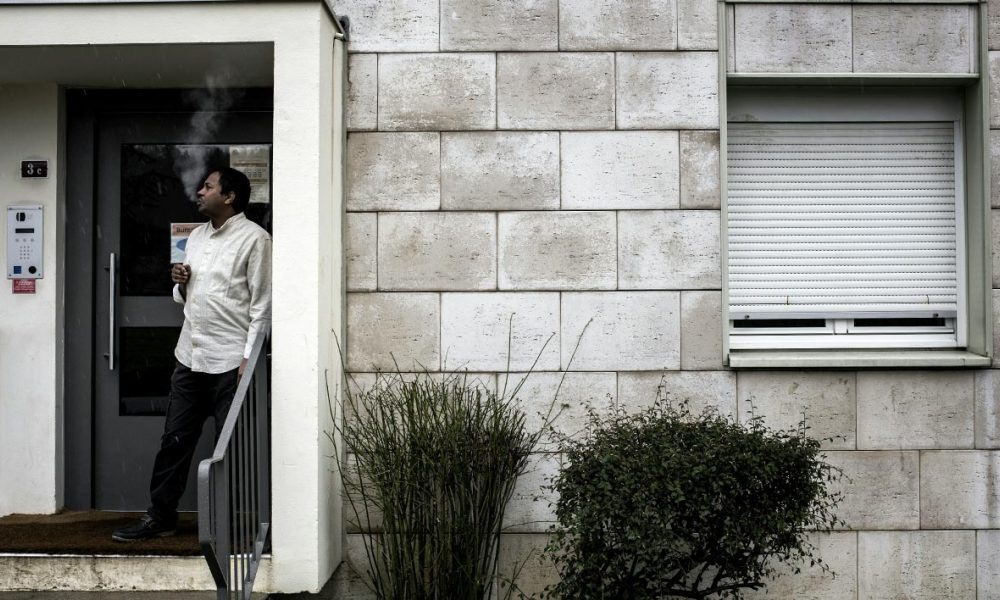 """Abdallah from Eritrea, who used to live in the """"Jungle"""" migrant camp in Calais, smokes a cigarette outside the Adoma home for refugees in Pouilly-en-Auxois on February 12, 2016. When a decision was made to move a group of asylum seekers to Pouilly-en-Auxois, residents were divided. A year on, the newcomers are slowly integrating into the French society."""