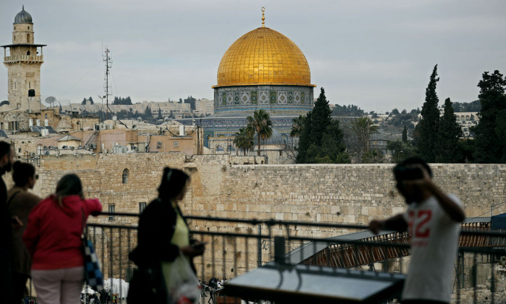 "People look out at a view of the Old City of Jerusalem, with the Dome of the Rock (C) in the Al-Aqsa mosque compound and the Western Wall below on December 5, 2017. The EU's diplomatic chief Federica Mogherini said that the status of Jerusalem must be resolved ""through negotiations"", as US President Donald Trump mulls recognising the city as the capital of Israel. THOMAS COEX / AFP"