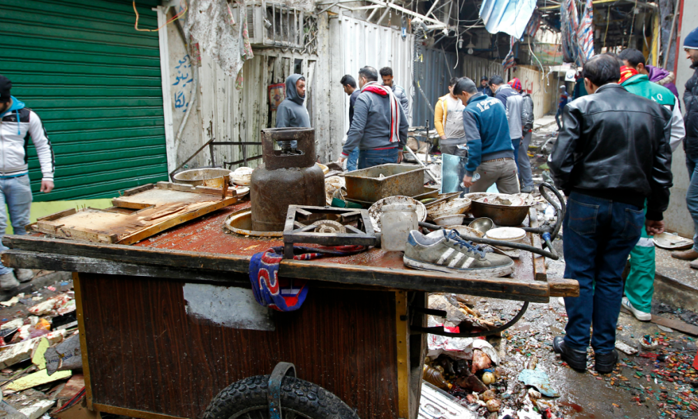 Iraqis look at the aftermath following a double bomb attack in a busy market area in Baghdad's central al-Sinek neighbourhood on December 31, 2016. Baghdad has been on high alert since the start on October 17 of an offensive, Iraq's largest military operation in years, to retake the northern jihadist stronghold of Mosul SABAH ARAR / AFP