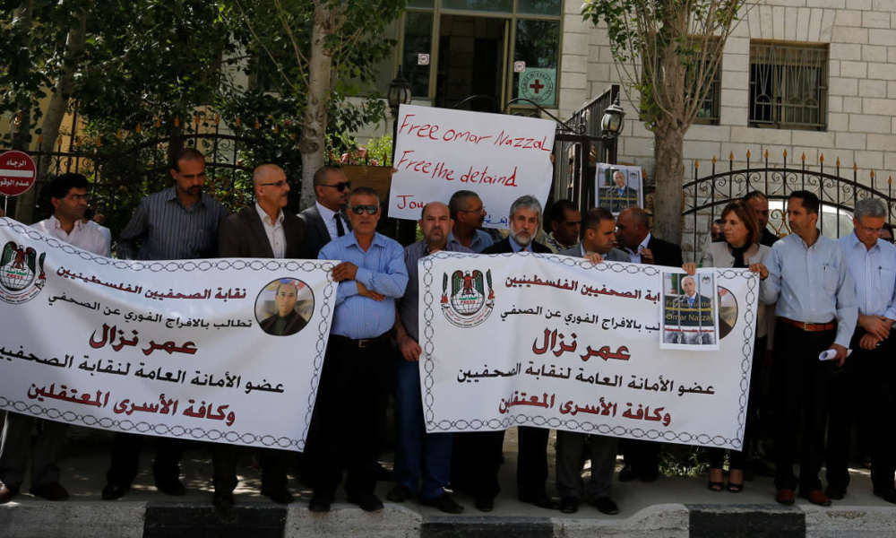 Palestinian journalists hold placards and banners during a demonstration on April 24, 2016, outside the Red Cross offices in the West Bank city of Ramallah, in support of their colleague, Omar Nazzal, who was detained the previous day by Israeli forces. Nazzal was detained by Israeli forces at the border with Jordan as he was on his way to Bosnia and Herzegovina for the general meeting of the European Federation of Journalists (EFJ).