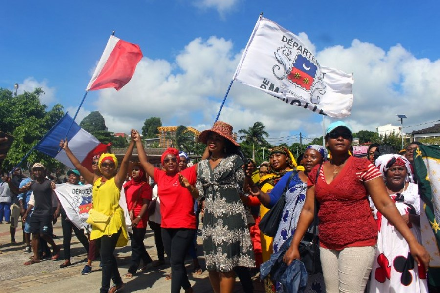 Protesters hold French and Mayotte flags as they gather on the Place de la Republique in Mamoutzou, on the French Indian Ocean island of Mayotte, on March 13, 2018, during a demonstration against insecurity and immigration. The French government attempted on March 12 to end weeks of unrest on the French Indian Ocean island of Mayotte, with a visiting minister promising action against insecurity and an influx of migrants from neighbouring African islands that has severely strained public services.