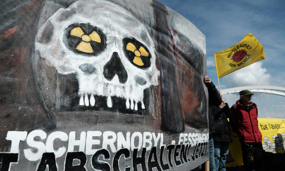 """Tchernobyl nucléaire activistes anti-nucléaire French and German anti-nuclear activists gather as they take part in the commemoration of the nuclear disaster in Chernobyl and to protest against the nuclear powerplant of Fessenheim, France's oldest nuclear reactor, on the """"Europe"""" bridge between Kehl, southwestern Germany, and Strasbourg, eastern France, on April 24, 2016. Ukraine on April 26, will mark the 30th anniversary of the Chernobyl disaster, when human error and flawed Soviet reactor technology led to the world's worst nuclear accident."""