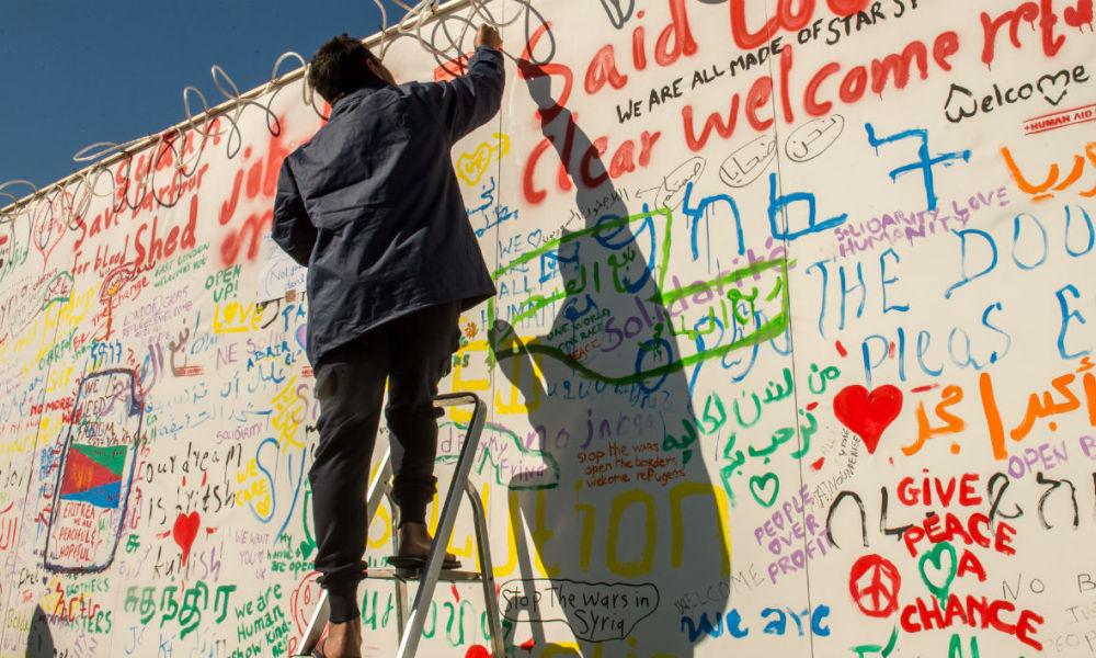 Un migrant inscrit un message sur un mur du terminal de ferry de Calais (photo d'illustration) -