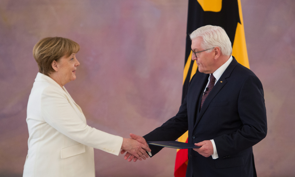 German President Frank-Walter Steinmeier (R) hands over the certificate of appointment to German Chancellor Angela Merkel on March 14, 2018 at Bellevue Palace in Berlin. Merkel, bruised by half a year of post-election coalition haggling, was elected by parliament to her fourth and likely final term at the helm of Europe's biggest economy. Stefanie LOOS / AFP