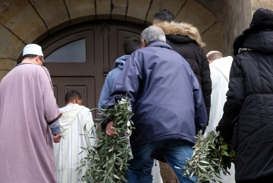 Muslim men (L) and other mourners carry olive branch wreaths as they arrive at the Saint Etienne Church in Trebes in southwest France for a service of remembrance on March 25, 2018, two days after a man carried out an attack in which four people were killed. Mourners in this rural French town rocked by a deadly Islamist attack held a mass on Palm Sunday to pay tribute to the victims, including a policeman hailed a hero for offering himself in place of a hostage. Lieutenant-Colonel Arnaud Beltrame, 44, was shot and stabbed after taking the place of a woman whom Radouane Lakdim had been using as a human shield during his attack Friday on a supermarket in the small town of Trebes.  ERIC CABANIS / AFP