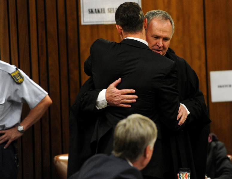 South African paralympic athlete Oscar Pistorius (L) greets his lawyer Barry Roux on October 17, 2014 before his sentencing hearing at the North Gauteng High Court in Pretoria. Pistorius, 27, was found guilty last month of culpable homicide over the killing of the 29-year-old law graduate, Reeva Steenkamp on Valentine's Day 2013, but was acquitted of murder. AFP PHOTO / POOL / WERNER BEUKES