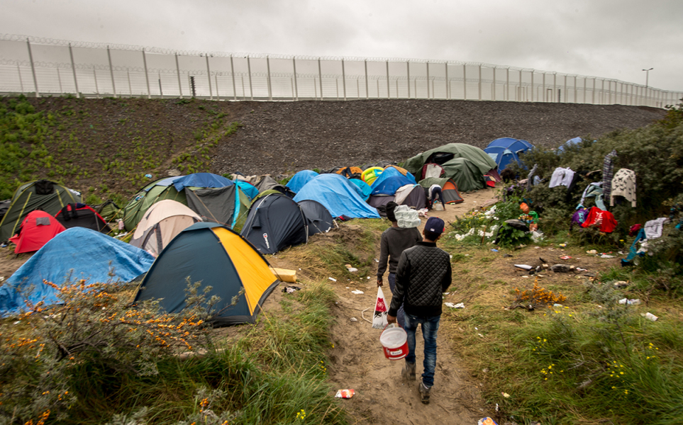 "A picture taken in Calais on October 7, 2015 shows a site dubbed the ""New Jungle"", where some 3,000 people have set up camp -- most seeking desperately to get to England, . The slum-like migrant camp sprung up after the closure of notorious Red Cross camp Sangatte in 2002, which had become overcrowded and prone to violent riots. However migrants and refugees have kept coming and the ""New Jungle"" has swelled along with the numbers of those making often deadly attempts to smuggle themselves across the Channel"