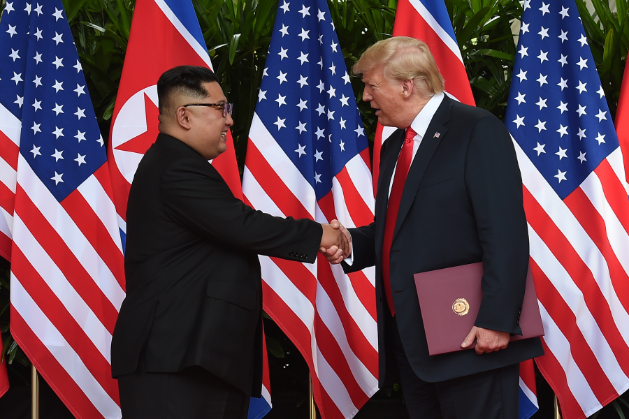 North Korea's leader Kim Jong Un (L) shakes hands with US President Donald Trump (R) after taking part in a signing ceremony at the end of their historic US-North Korea summit, at the Capella Hotel on Sentosa island in Singapore on June 12, 2018. Donald Trump and Kim Jong Un became on June 12 the first sitting US and North Korean leaders to meet, shake hands and negotiate to end a decades-old nuclear stand-off. Anthony WALLACE / POOL / AFP