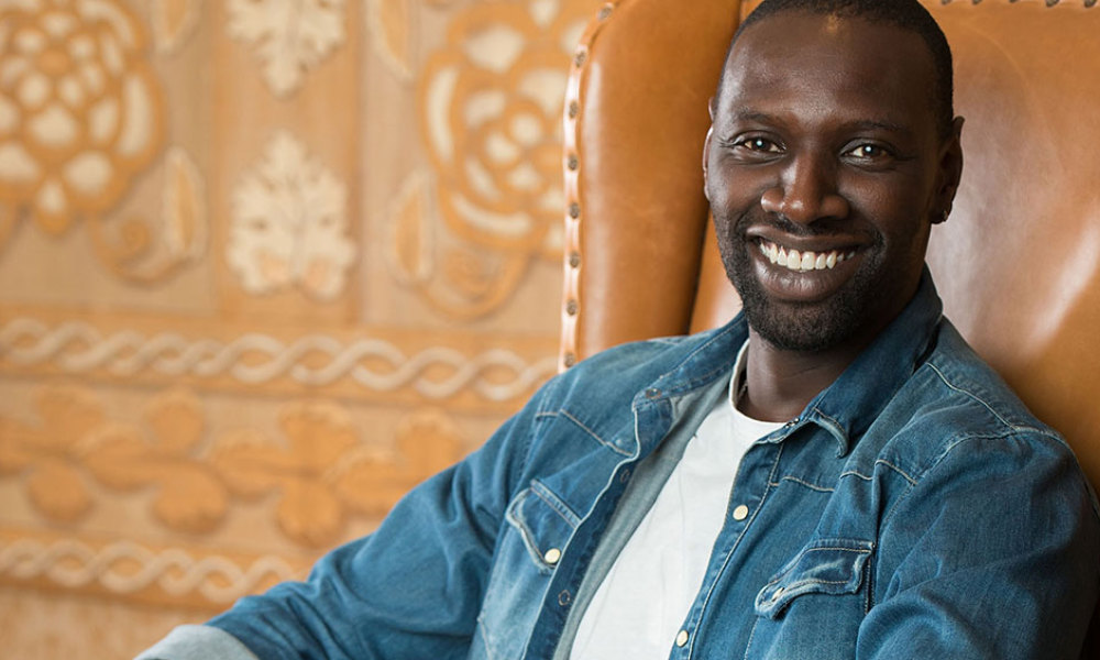 "French actor Omar Sy poses during the press day for the movie ""Samba"", in Beverly Hills, California, on July 20, 2015. Sy has come a long way from the gritty Paris suburbs where he grew up. But sitting in a five-star Beverly Hills hotel he has clearly not forgotten his immigrant roots. And the same goes for his career -- weeks after starring in the record-breaking ""Jurassic World"" blockbuster franchise, he will be on US cinema screens in his latest French film, ""Samba."""