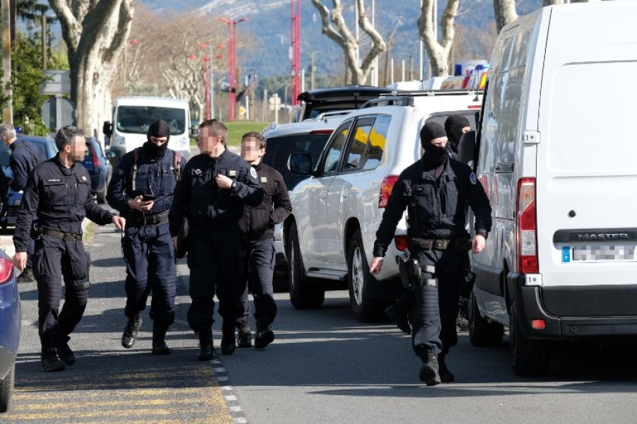 French National Gendarmerie Intervention Group (GIGN) walk next to vehicles as they gather outside the Super U supermarket in the town of Trebes, southern France, where a man took hostages killing at least two before he was killed by security forces on March 23, 2018. Security forces killed a gunman who first hijacked a car in nearby by Carcassonne, killing a passenger and injuring the driver, before shooting a policeman who was out jogging with his colleagues nearby. He then drove to a Super U supermarket in the town of Trebes and holed up there for more than three hours with hostages, killing at least two other people, according to sources.