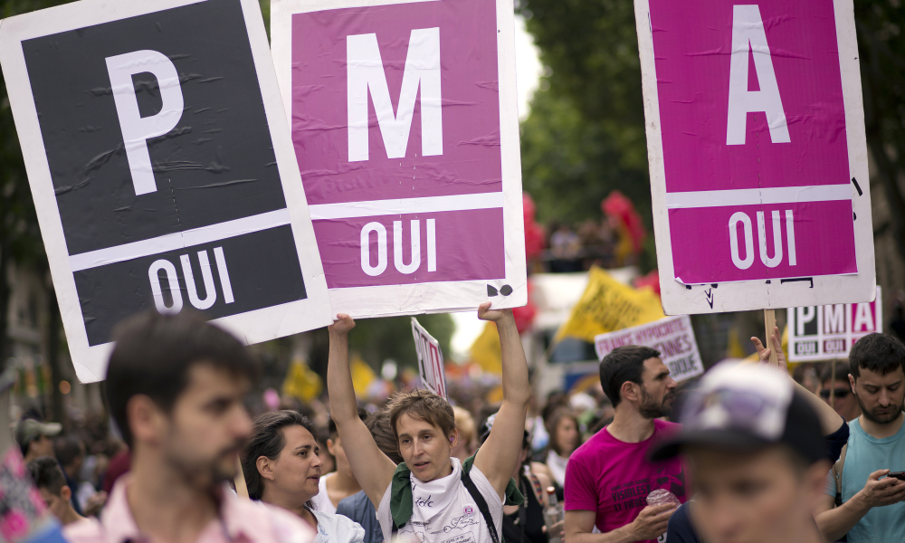 """People parade with placards reading """"assisted medical procreation, Yes"""" (PMA in French) during the homosexual, lesbian, bisexual and transgender (HLBT) visibility march, the Gay Pride, on June 29, 2013 in Paris. AFP PHOTO / LIONEL BONAVENTURE LIONEL BONAVENTURE / AFP"""