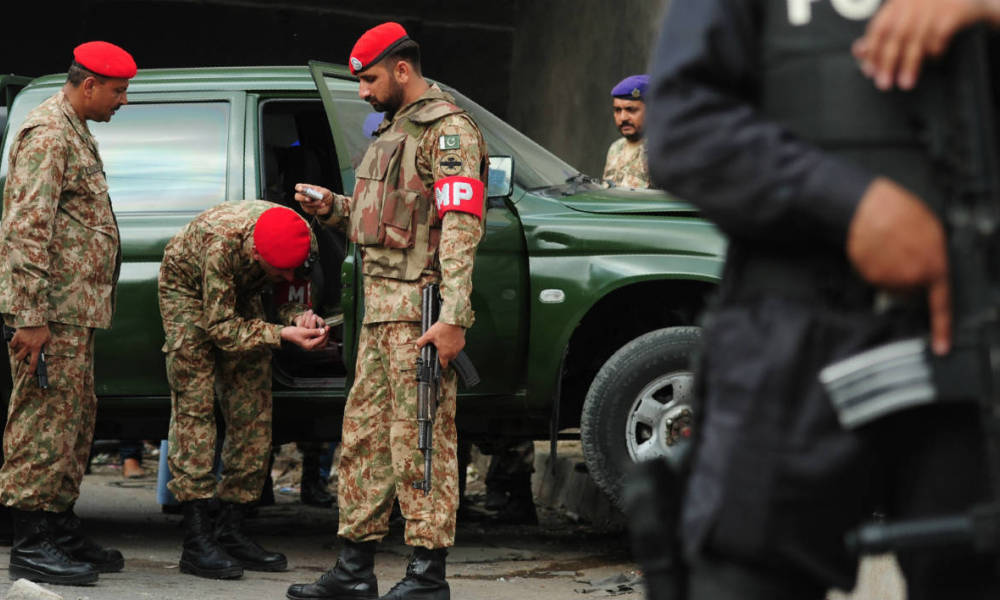 Pakistani troops examine an army vehicle at the site of an attack by gunmen in Karachi on July 26, 2016. Two Pakistani soldiers were shot dead on July 26 when two gunmen on a motorcycle opened fire on their pick-up truck in the southern city of Karachi, officials said.